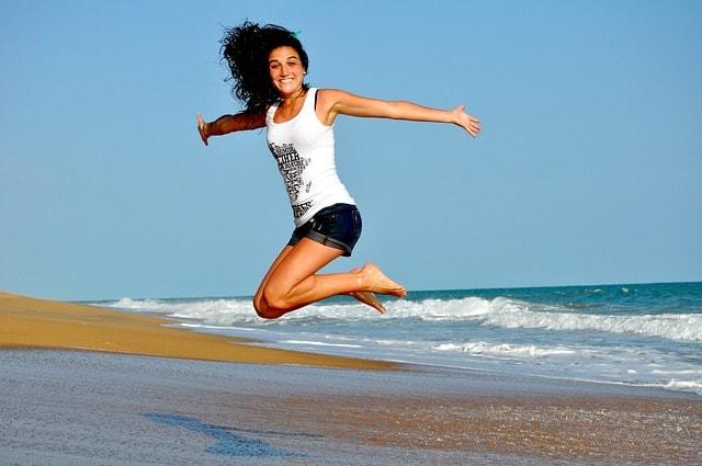 žena skákající radostí na břehu moře