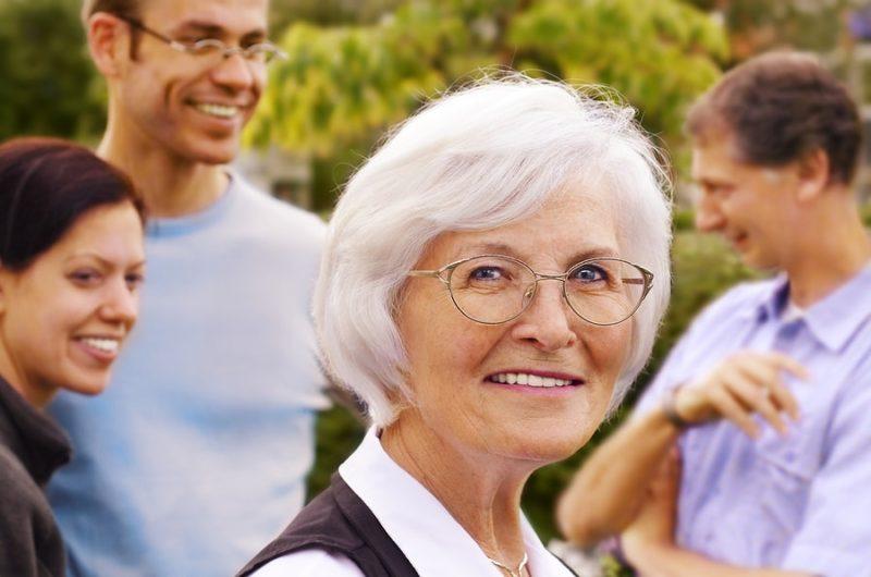 skupinka veselých lidí se starší ženou vepředu